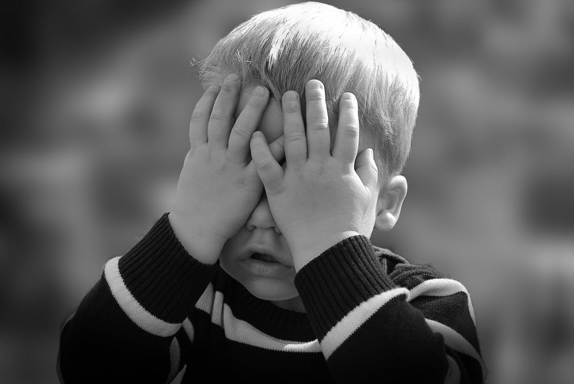 Boy in Black and White Sweater Covering His Face With His Tow Hand