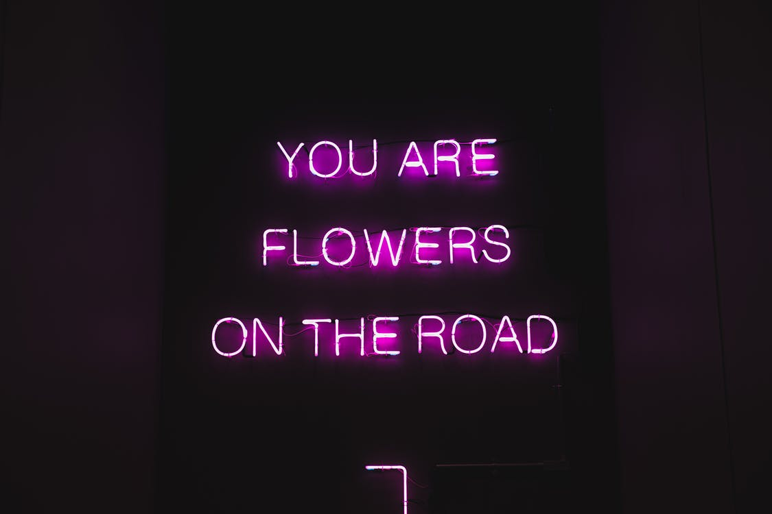 Pink color neon luminous text with inspiring phrase You are flowers on the road on black signage at night