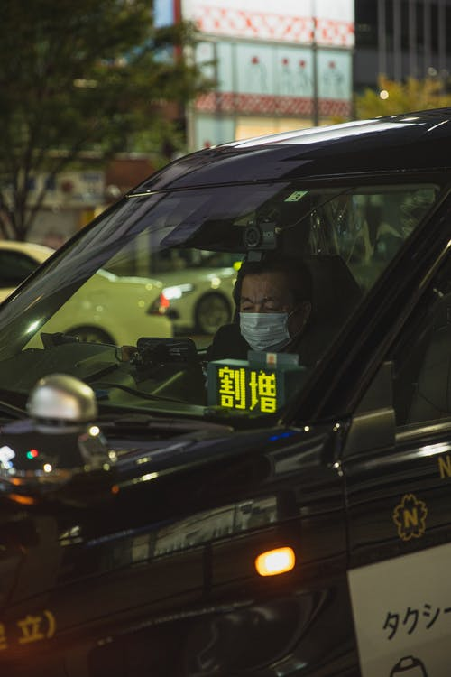 Asian man wearing mask in car