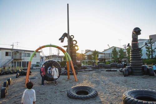 Small yard with huge monster creature figures constructed of old tyres on playground full of children
