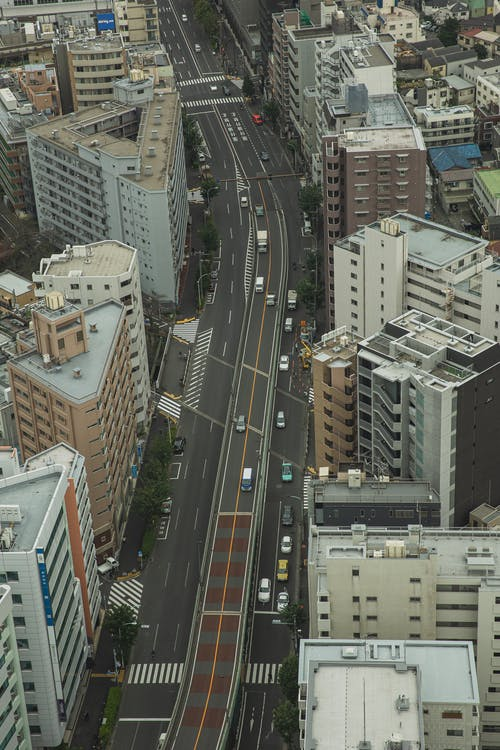 Aerial view of modern city with multistory buildings and wide roadway full of transport