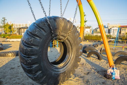 Swing made of huge rubber tyre for kids located on playground in suburb yard
