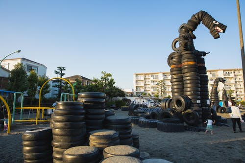 Pile of tyres on playground in city