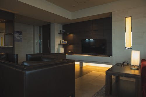 Interior of modern apartment with comfortable leather sofa and armchairs and other modern furniture and tv