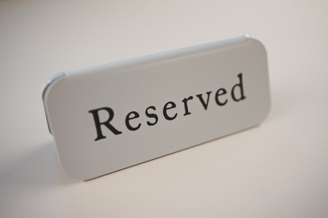 Metal signage with black letters saying Reserved on gray background used in cafes and restaurants