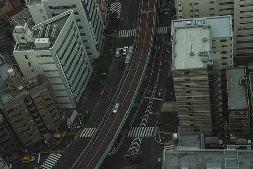 Drone view of residential area in modern city with transport on asphalt roads and multistory houses