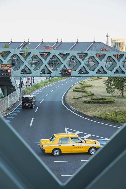 Yellow taxi car driving along asphalt roadway under pedestrian overpass in contemporary city district