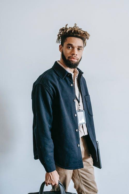 Stylish black man with briefcase in studio