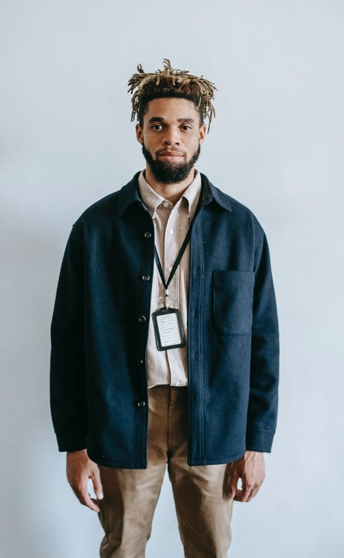 Confident calm African American male with dreadlocks wearing stylish outfit and neck cardholder standing against white wall in light studio and looking at camera