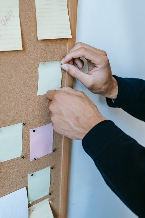Crop unrecognizable male attaching colorful memo papers with thumbtacks to cork bulletin board hanging on white wall in office
