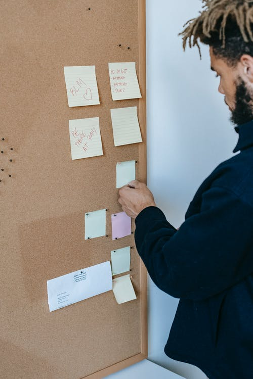 Serious ethnic guy reading sticky notes attached to pinboard