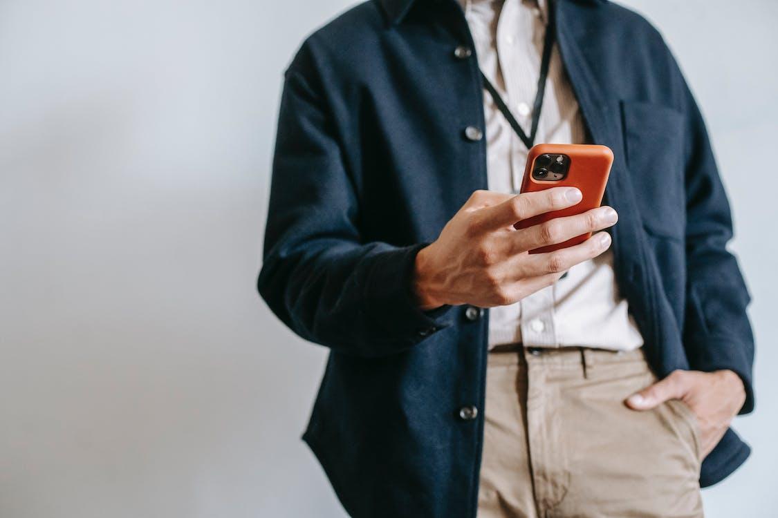 Faceless male entrepreneur using smartphone against white background