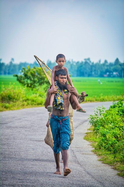 Man in Brown Shirt Carrying Woman in Brown Dress on Gray Asphalt Road