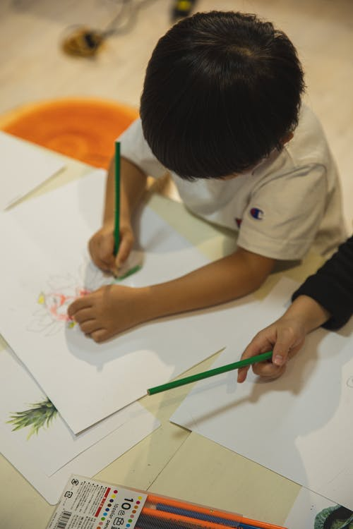 High angle of crop anonymous ethnic children drawing on paper sheet with pencils during art class in kindergarten