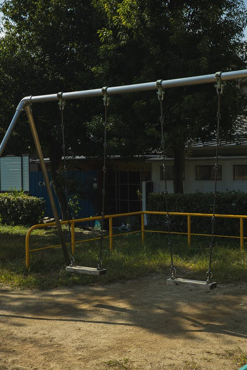 Metal empty swings on playground in yard among green trees on sunny summer day