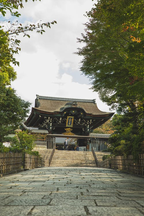 Exterior of oriental shrine behind pavement walkway in garden with green foliage on trees