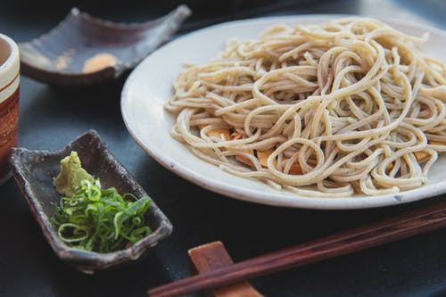 Appetizing pasta near wakame and wasabi