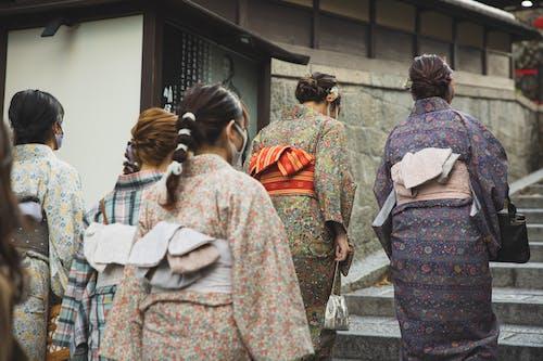 Unrecognizable Asian women walking on street