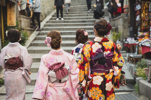 Back view of unrecognizable women with neat hairstyle in traditional kimonos walking on paved street in oriental city