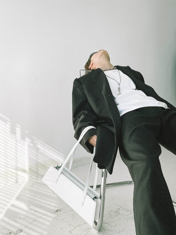 Stylish woman wearing suit lying on chair