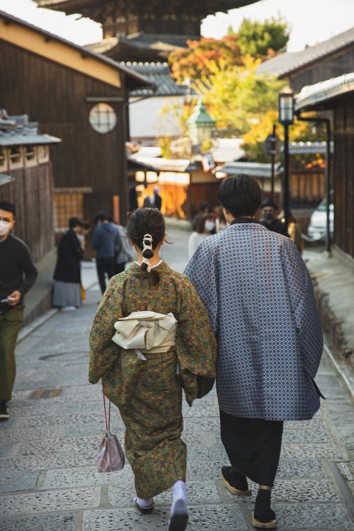 Back view faceless pedestrians wearing traditional Japanese clothed strolling on narrow paved street in sunny Asian town