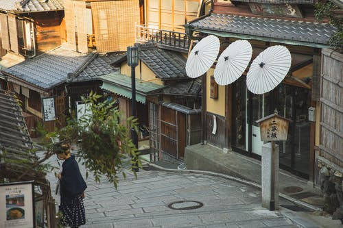 From above of unrecognizable female tourist standing on paved walkway near aged typical houses in Higashiyama district of Kyoto
