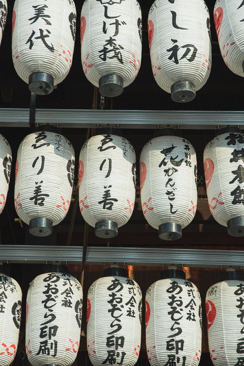 Row of traditional Japanese lanterns decorating exterior of ancient shrine