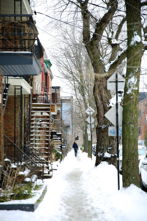 Anonymous person strolling on snowy sidewalk in city