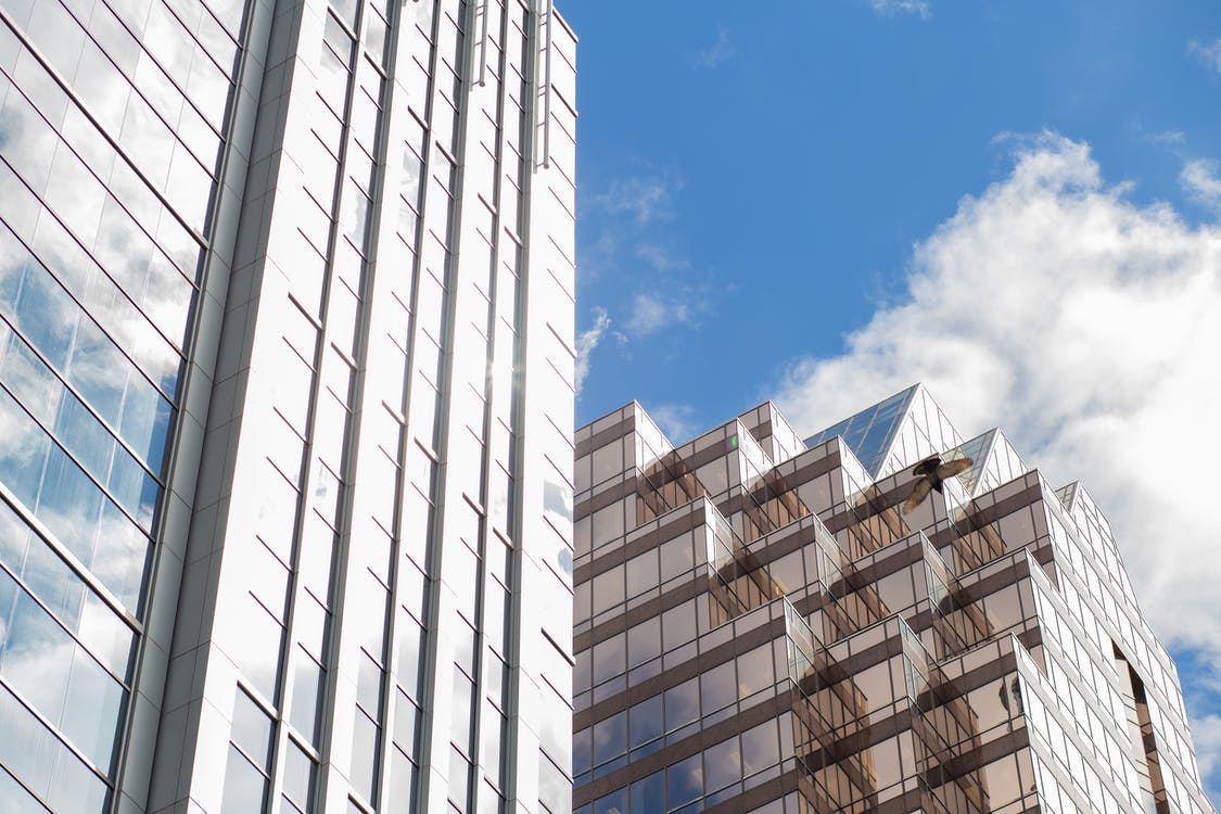 Low angle exterior of modern building and skyscraper with glass mirrored walls located on city street against cloudy blue sky in sunlight