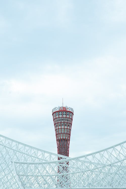 From below of famous Kobe Port Tower located near contemporary geometric building in Japan