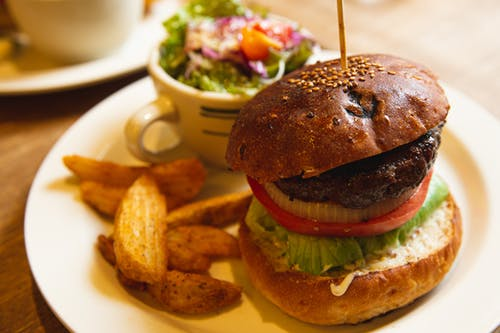 Delicious burger with vegetables and fries