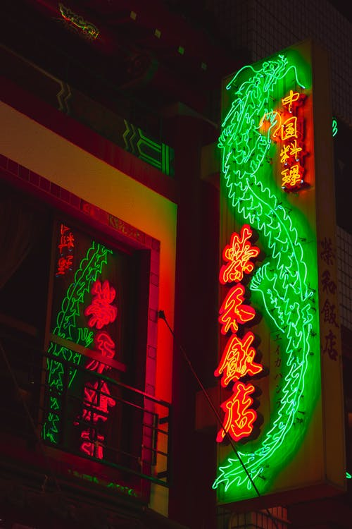 From below of illuminated sign with bright Chinese hieroglyphs hanging outside building at night