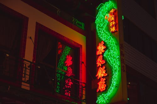 From below of bright glowing neon signboard in oriental style hanging on facade of building at night