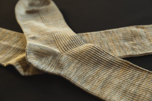 From above of pair socks made of soft material placed above each other on black background