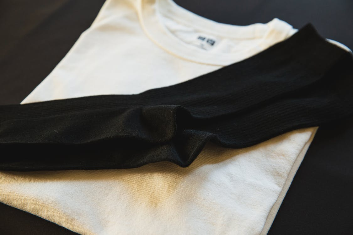 From above of new white folded cotton wear with pair of black socks for man