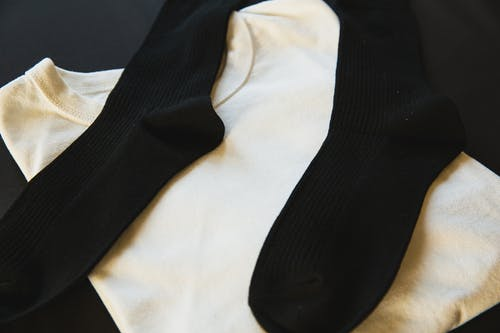 High angle of white folded male t shirt with pair of black cotton socks