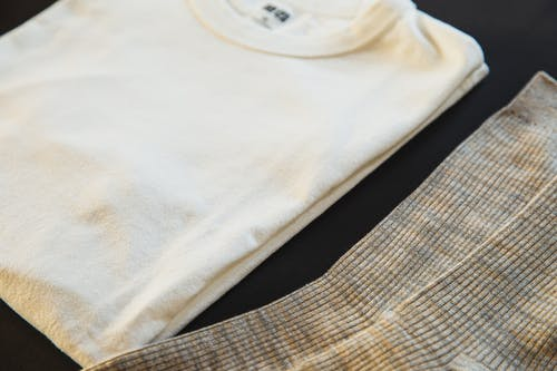 High angle of white folded cotton t shirt with round shaped neckline near striped socks for man on black background