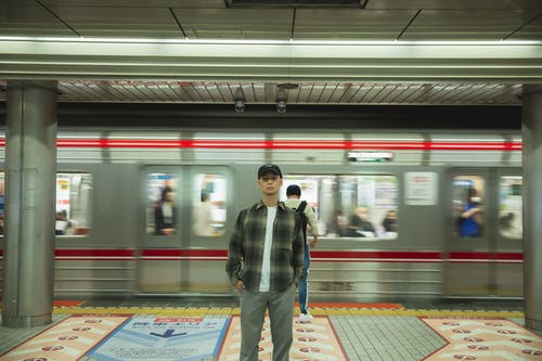 Asian man standing on platform in underground