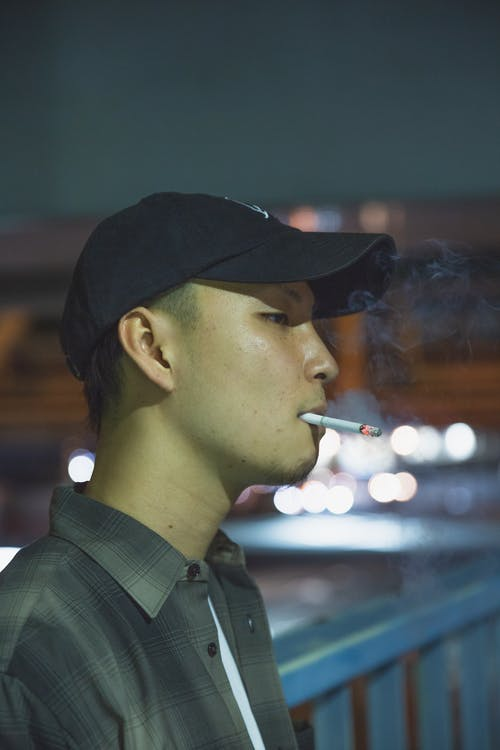 Side view of Asian male smoker with cigarette standing near fence at night and looking away
