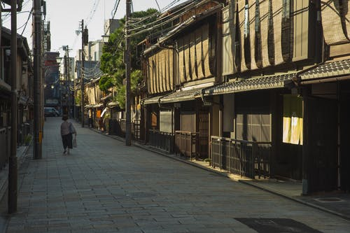 Unrecognizable woman walking near traditional houses in Japan