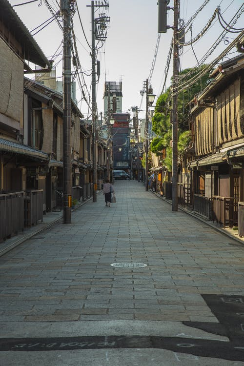 Anonymous female walking on Kyoto street in morning