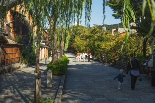 Anonymous people strolling in old city district near wooden houses and green trees