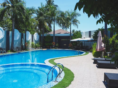 Outdoor swimming pool with sunbeds on territory of tropical hotel with green palm trees against cloudless blue sky