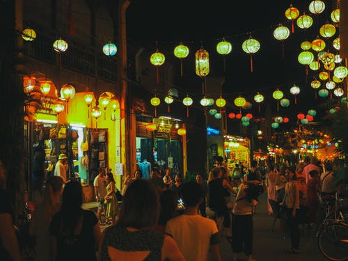 Anonymous people walking and spending time on city street decorated with Asian paper lanterns near touristic shops and cafes at night