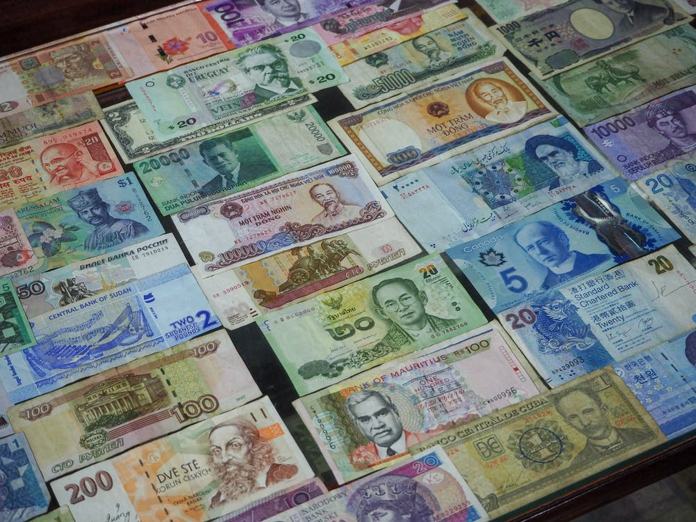 From above collection of various colorful banknotes from different countries arranged in row on table