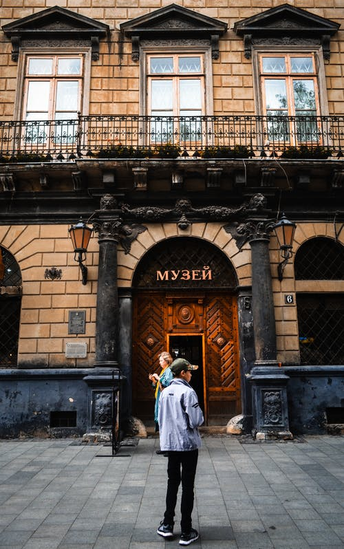 Unrecognizable people standing on street against entrance to museum in old building with ornamental walls in daytime