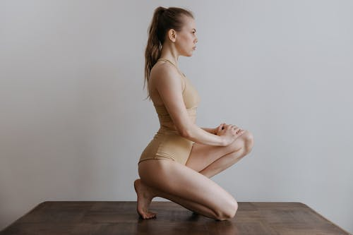 Woman in Beige Spaghetti Strap Dress Sitting on Brown Wooden Floor
