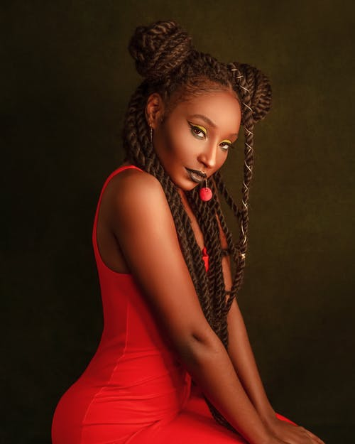 Side view of eccentric trendy African American female model in red dress with creative braided hair sitting and looking at camera against brown background