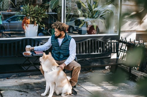 Serious black man with coffee on bench near dog