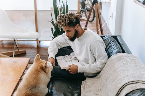 Black man sitting with book near dog